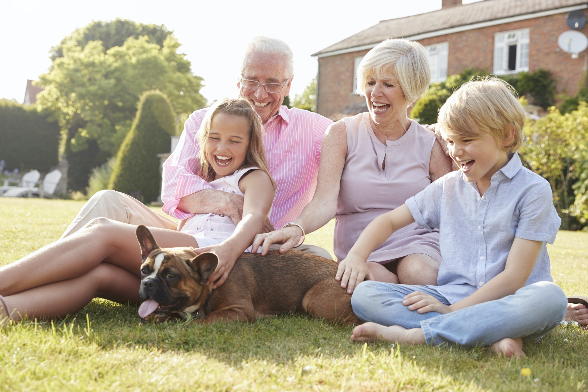 Grandparents and grandchildren sitting in garden with dog